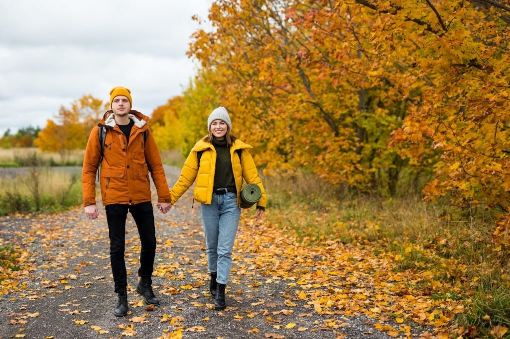 Couple of hikers with backpacks walking in autumn forest with yellow and orange colored leaves
