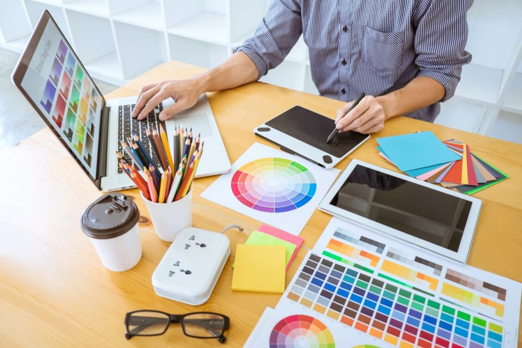 Creative graphic designer looking at color palette and selecting harmonious color combinations