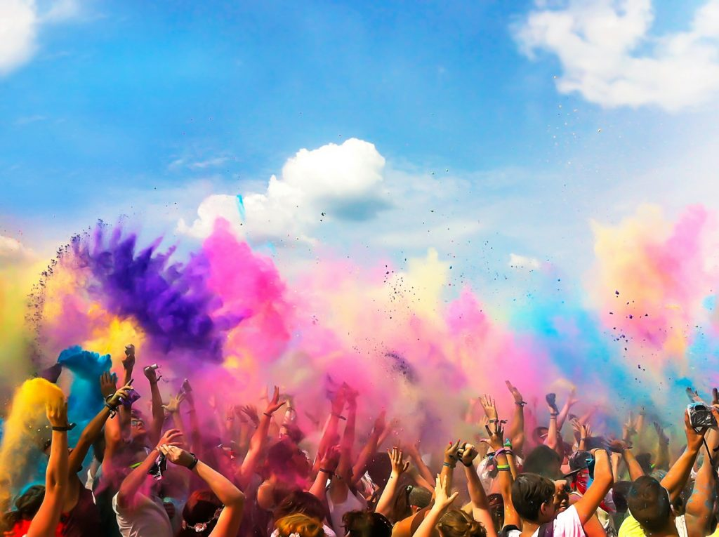 Crowd of people throwing colored powder in the air at Holi festival