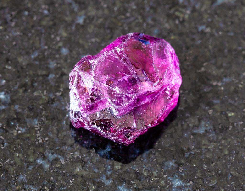 Close up of dark pink rhodolite Garnet on a black granite background