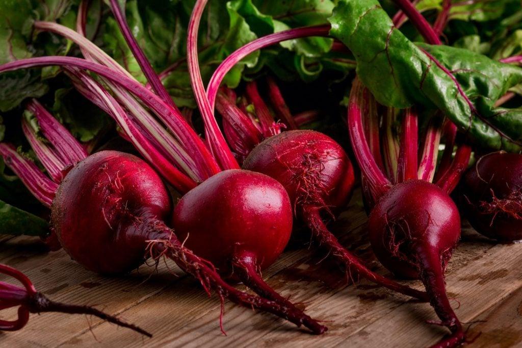 Dark red organic beetroot on wooden background