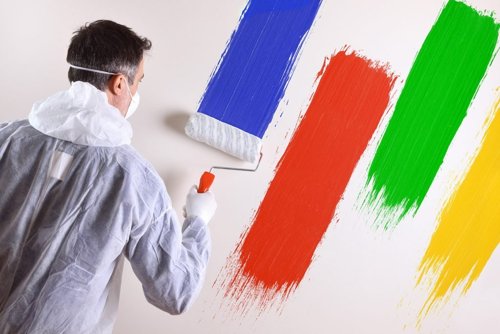 Painter with overalls and wall painted in square colors red, green, yellow-orange and blue-violet