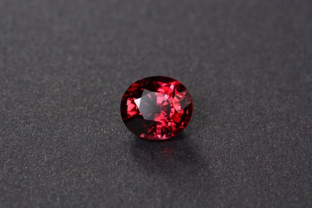 Deep red rhodolite garnet gemstone on a dark background