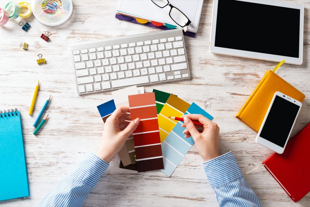 Designer choosing colors from swatches at wooden desk. Office workplace with computer keyboard.