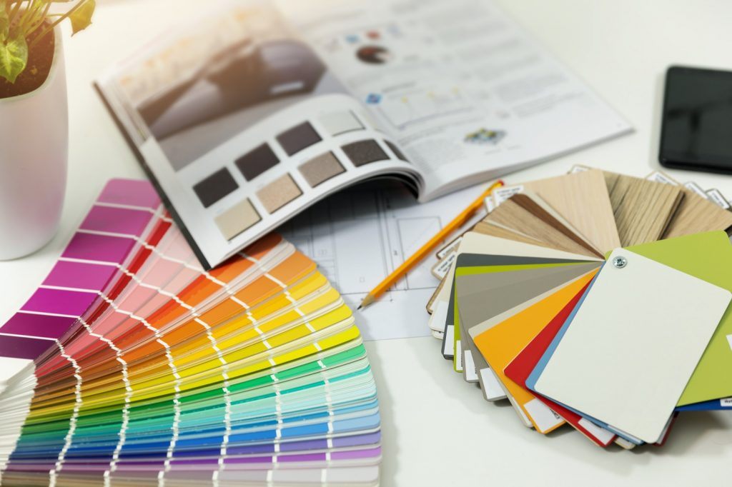 Designer workplace with interior paint color swatches and furniture material samples