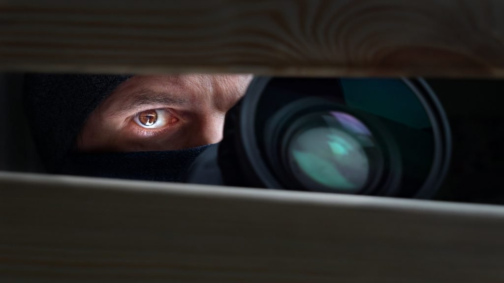 Detective with camera looking through hole between wooden boards