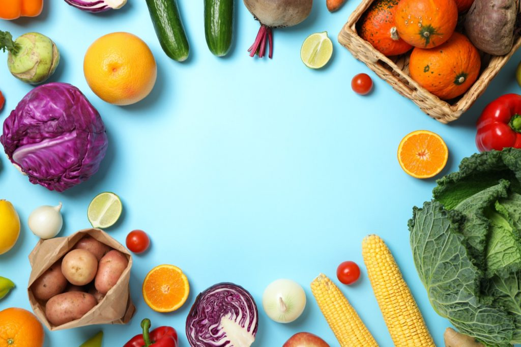 Different vegetables and fruits on blue colored background