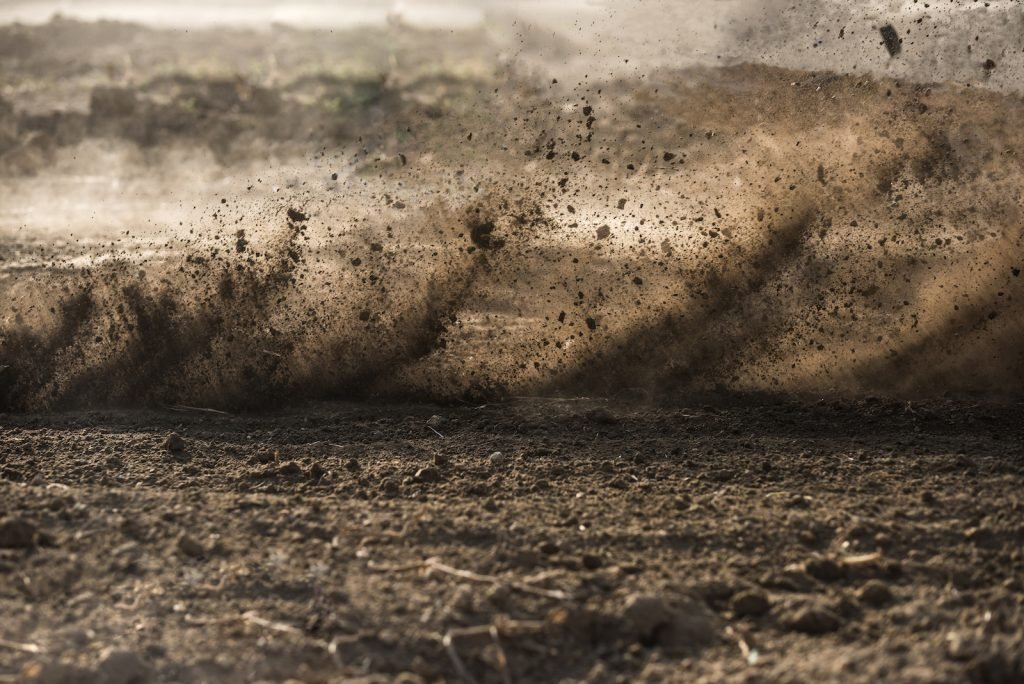 Dirt on the ground and in the air after motocross driving past at high speed