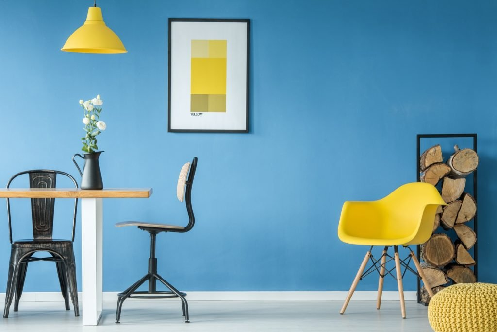 Dominating blue colored wall and yellow accents in dining room