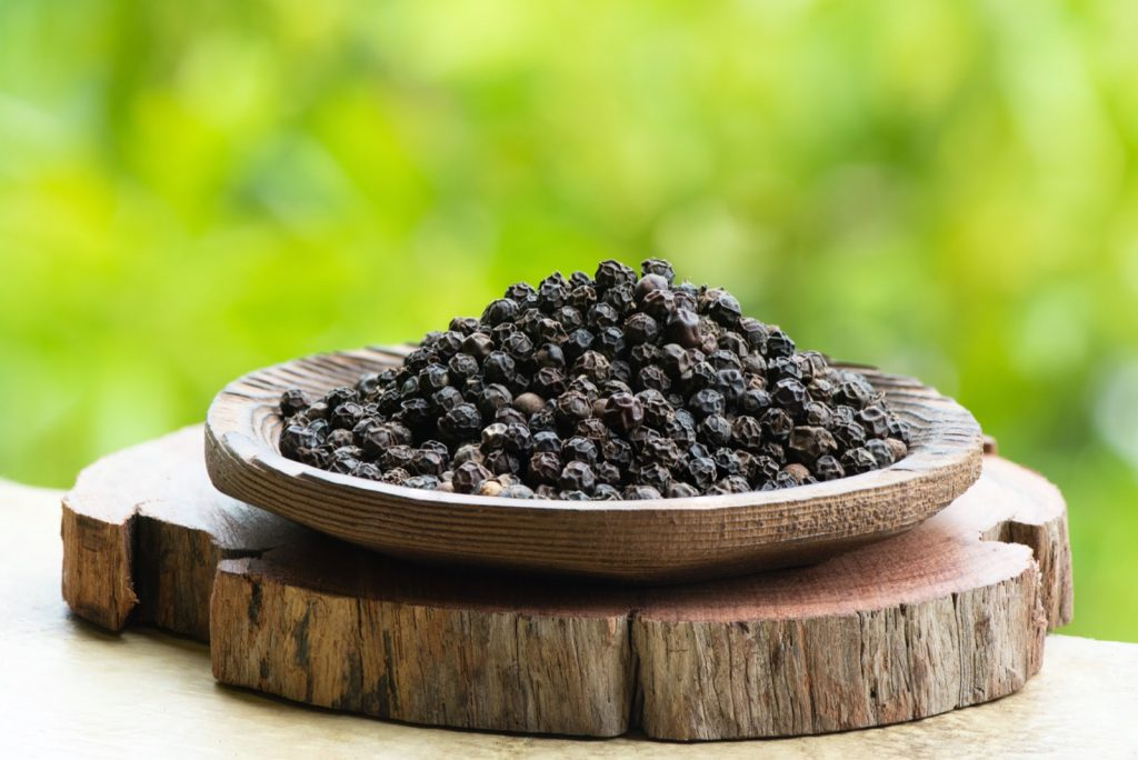 Dried black pepper on nature background