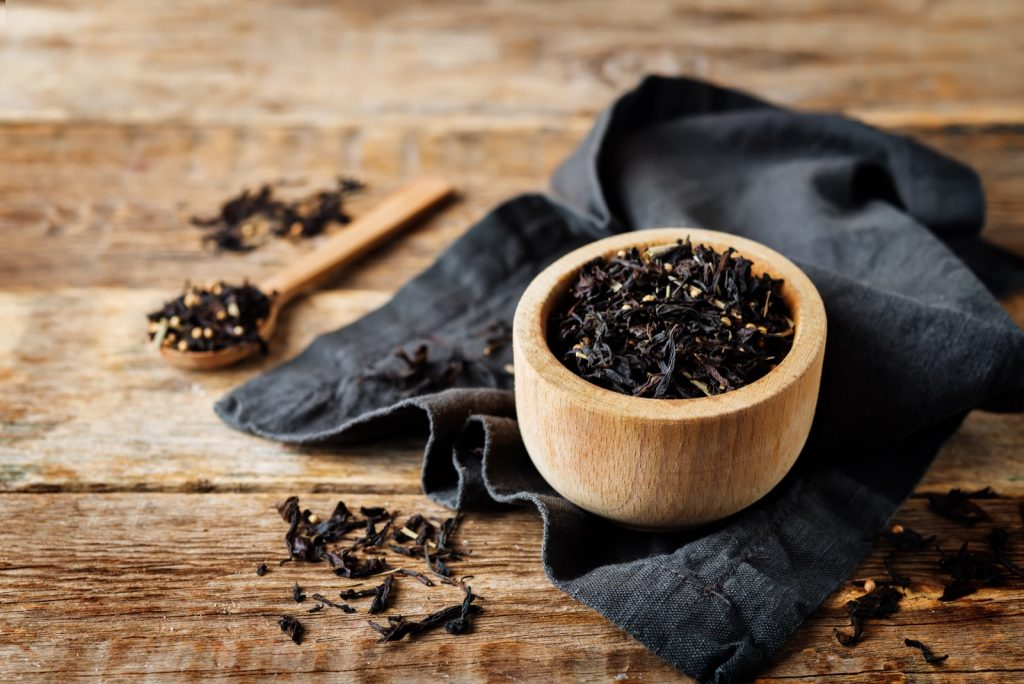 Dried black tea with spices in a spoon and a bowl