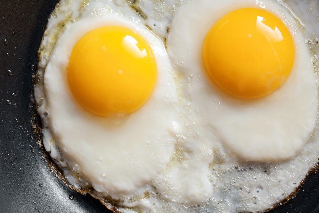 Two fried eggs with bright yellow yolks in a black frying pan
