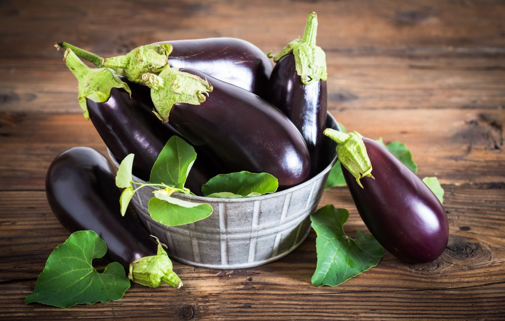 Bunch of fresh eggplants in a metal basket standing on a dark wooden table