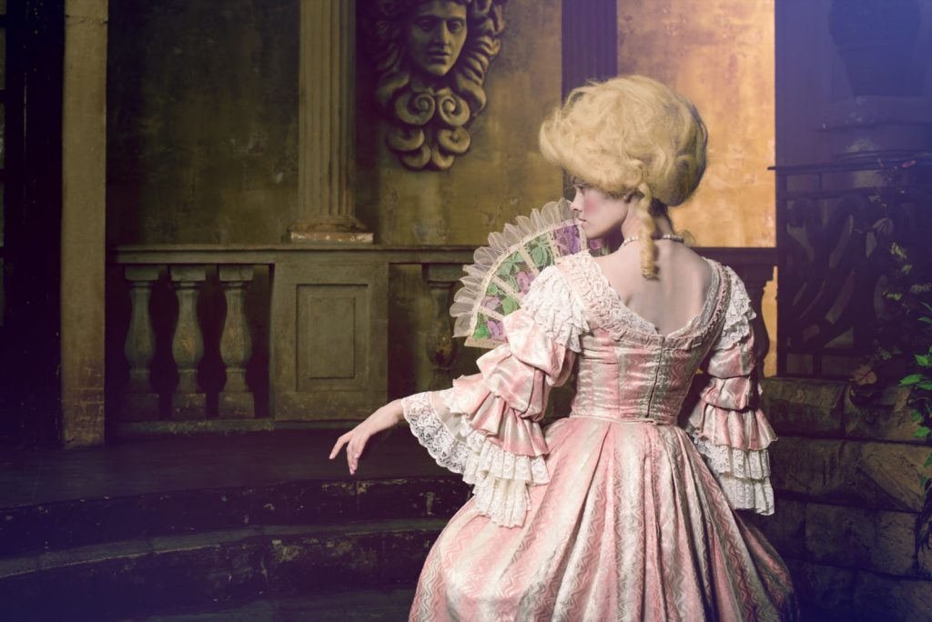 Eighteenth century victorian woman in pink dress posing in vintage exterior