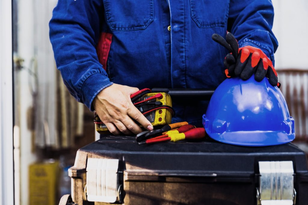 Electrical engineer holding multimeter, tools and blue hard hat