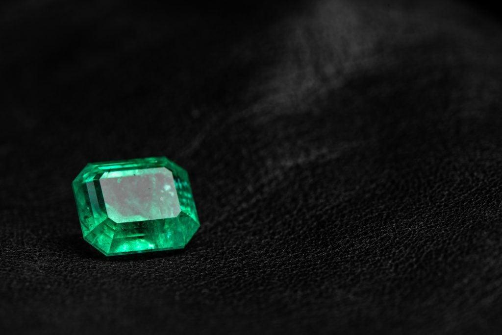 Green emerald gemstone on black background