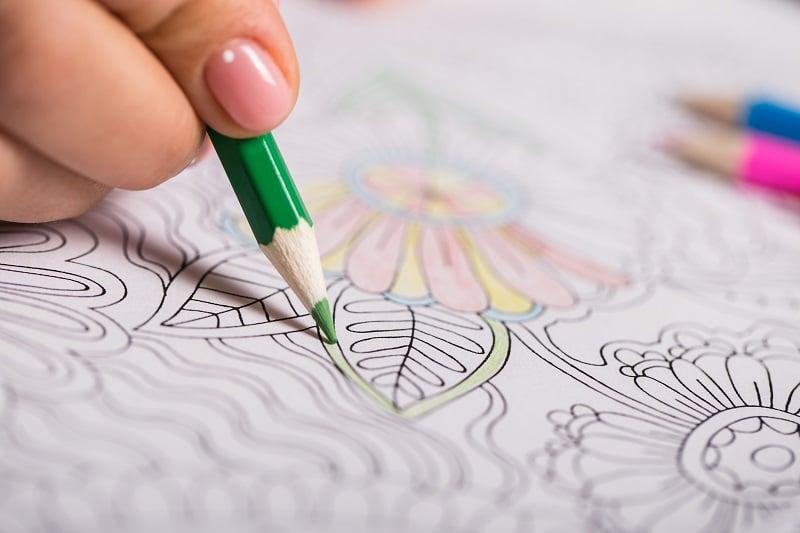 Hand with pencil coloring mandala