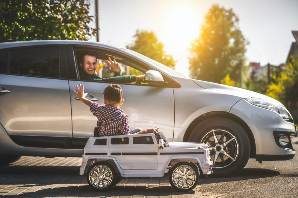 Father in his silver car and his little son driving a small silver toy car