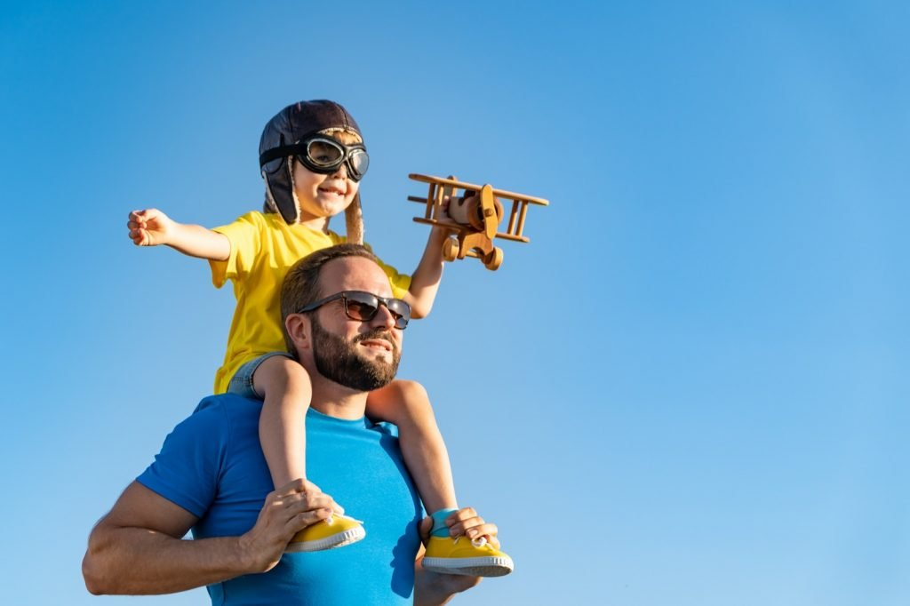 Father and son playing with a wooden plane under a blue summer sky