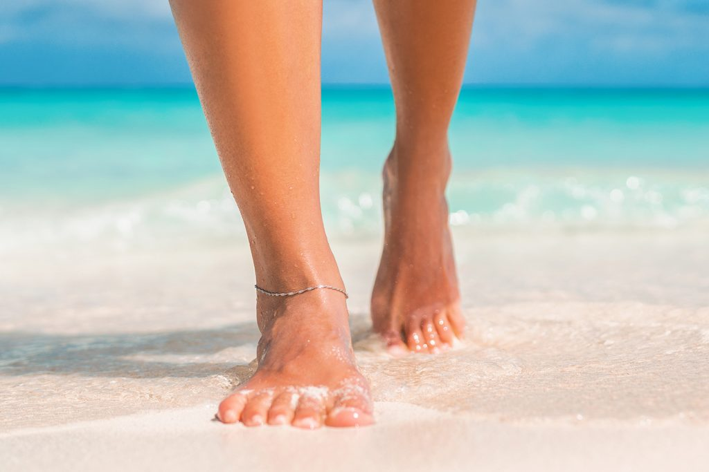 Woman feet with reflective jewelry walking on beach near the water