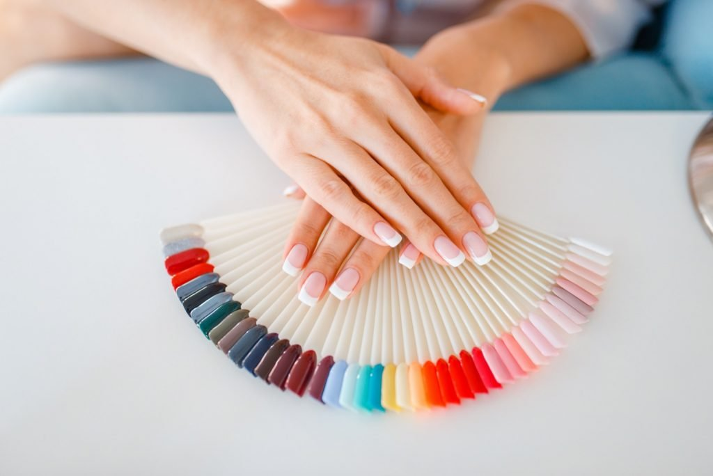 Female hands on top of colorful nail varnish palette