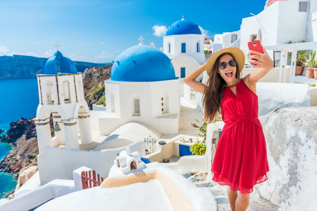 Female tourist taking selfie photo with phone at famous three blue domes church in Santorini Greece