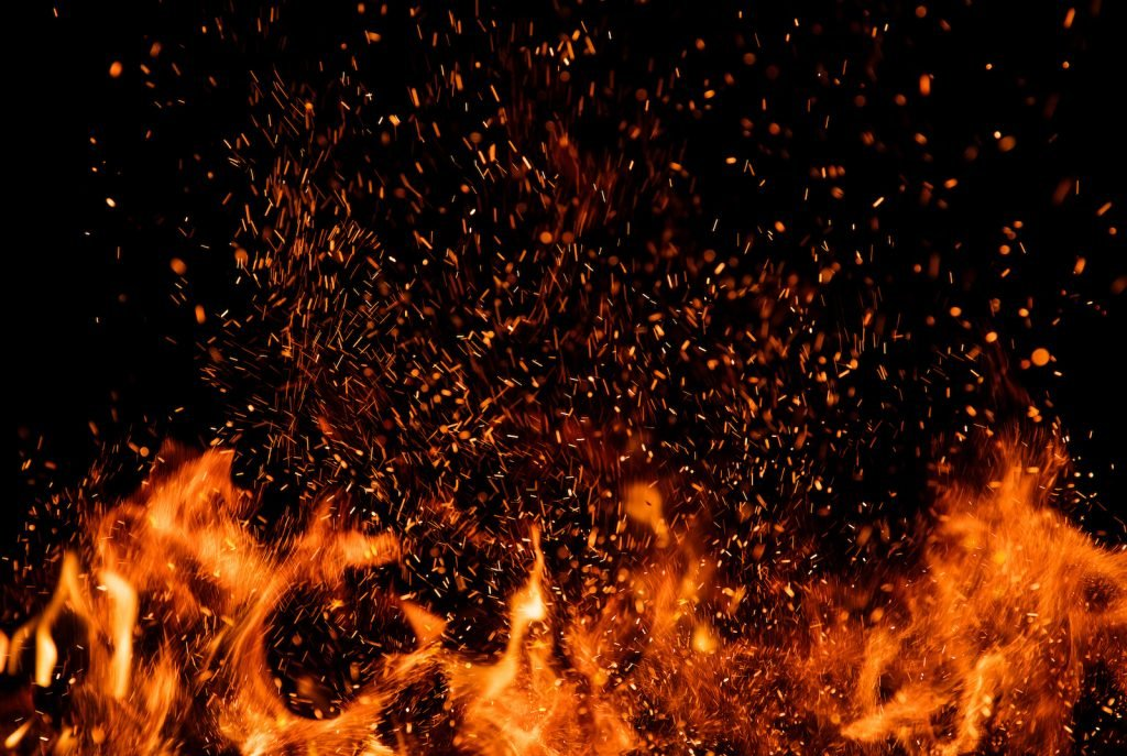 Closeup of bonfire with fire sparks flying in the air with the pitch black night sky in the background