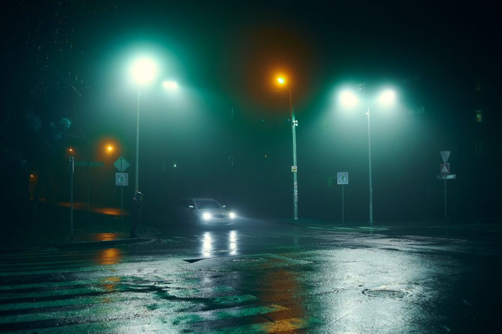 Fog and rain at night in the city with barely visible car