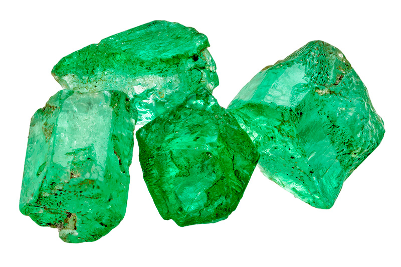 Four emerald crystals isolated on white background