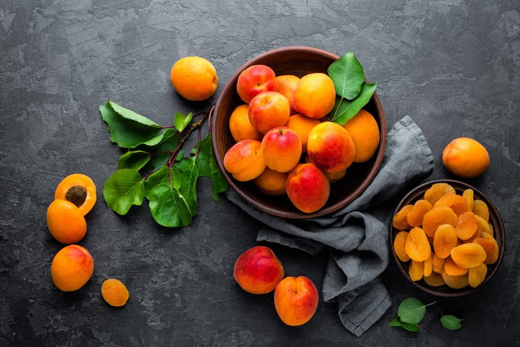 Top view of fresh and dried apricots on a black background