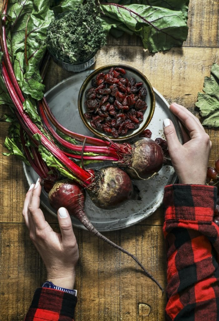 Vegan fresh cooking ingredients on a wooden table. Red beetroot and dried cranberries