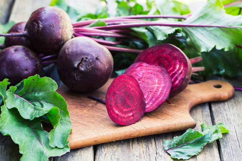 Fresh beetroots on a wooden chopping board one is cut in fine slices