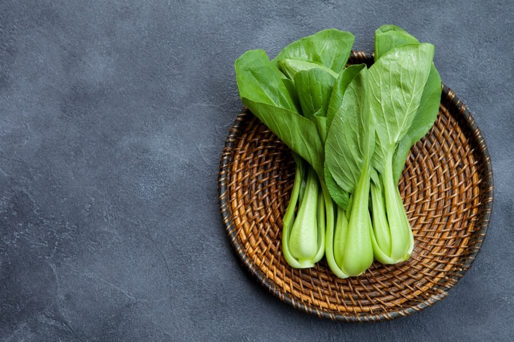Fresh green bok choy salad on a wooden plate