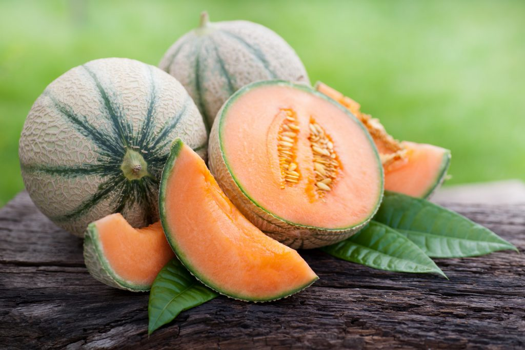 Two whole and one sliced fresh cantaloupe on a wooden surface with a green blurred background