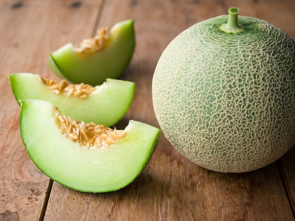 Fresh cut and whole honeydew melon on a rustic wooden table