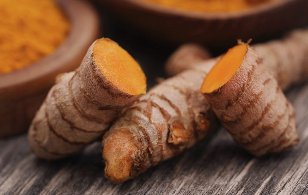 Closeup of fresh raw turmeric with blurred background of turmeric powder in a bowl