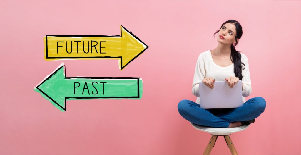 Woman with laptop computer sitting in front of pink wall with the written words future and past