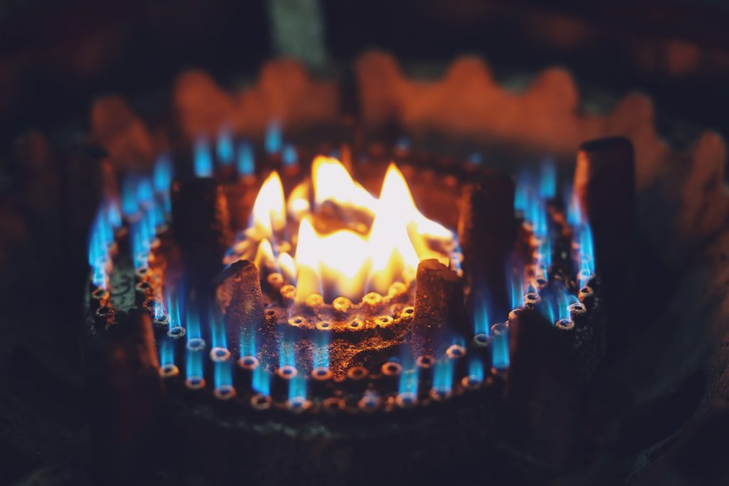 Burning gas stove burner hob with a light yellow flame and smaller blue flames surrounding it