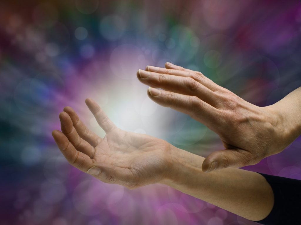 Energy of orb between hands on a dark colored background