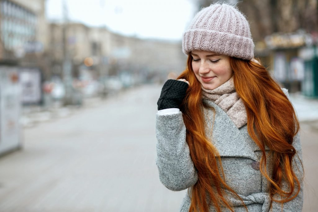 Young woman with long ginger hair standing outside in the cold weather