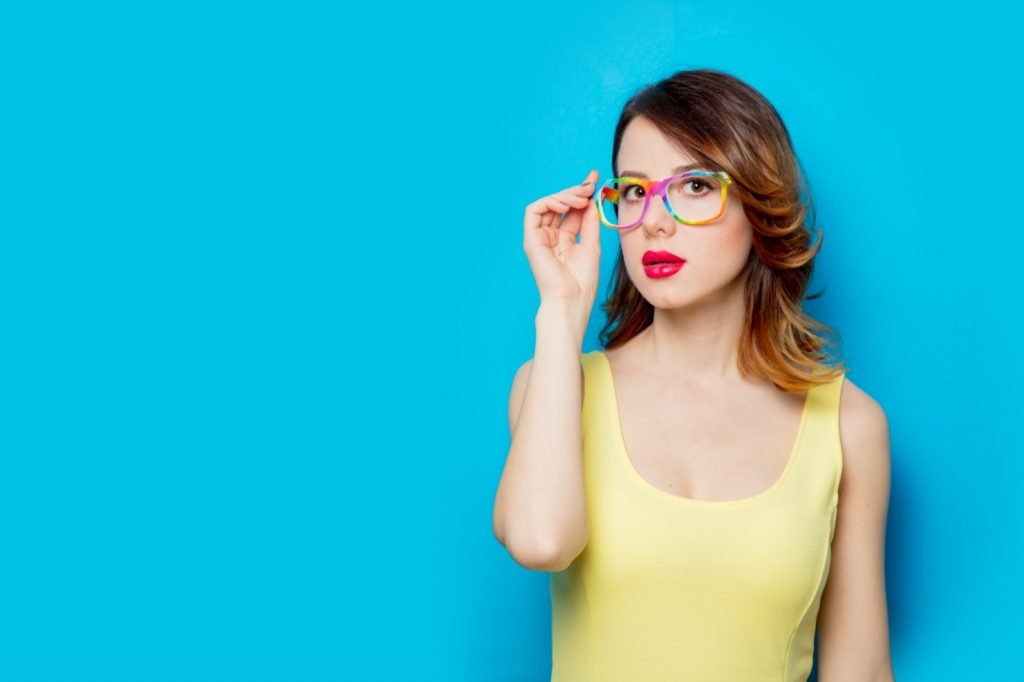 Redhead girl in yellow shirt and colored glasses on blue background