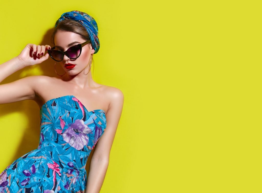 Girl in bright blue dress with headscarf and sunglasses in front of yellow wall