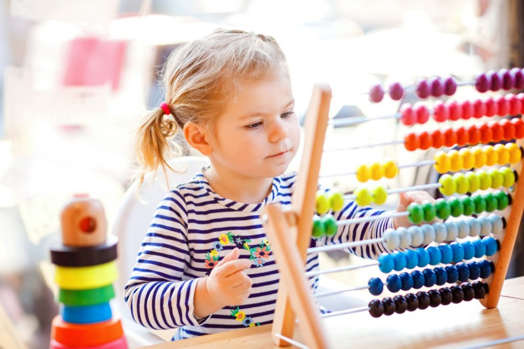 Girl learning colors with wooden rainbow toy pyramid and counter abacus