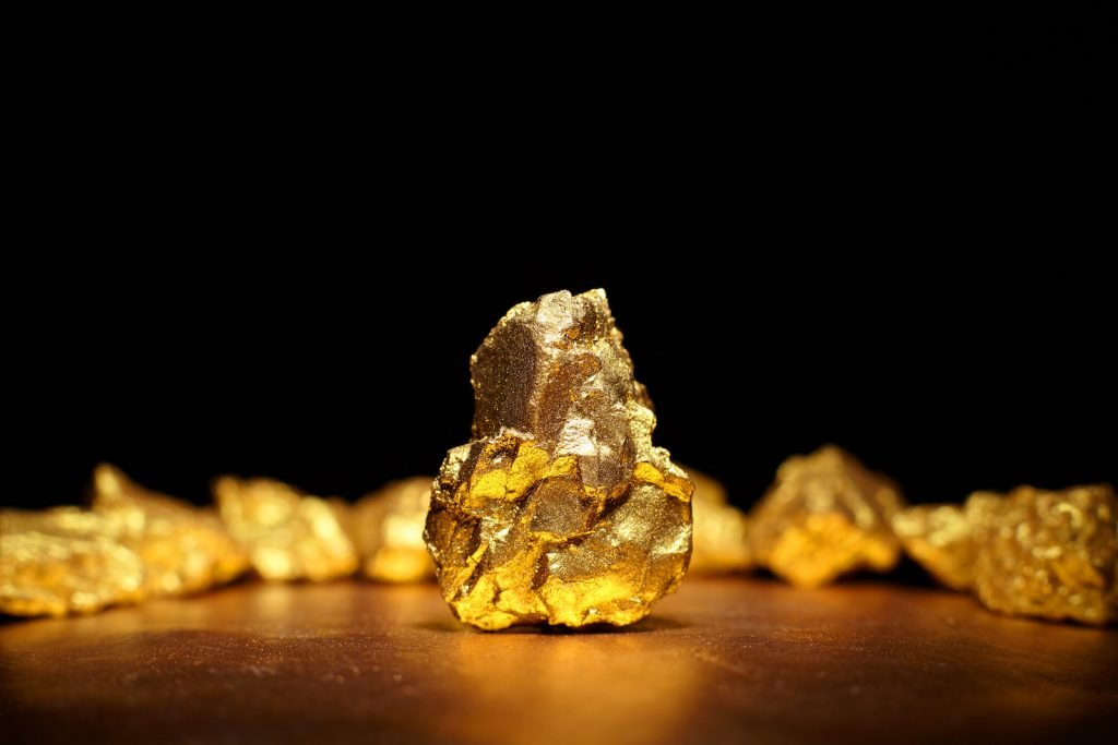 Closeup of big gold nugget standing on a table with light from above and pitch black background