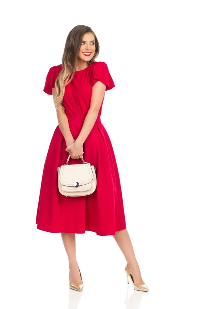 Woman in red dress and gold high heels holding beige purse