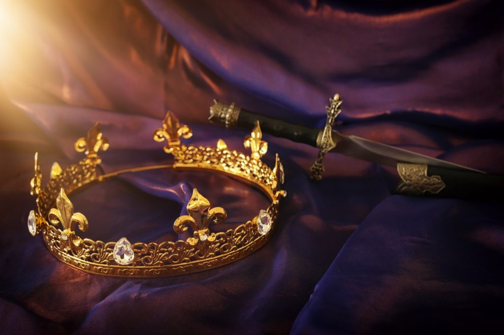 Golden crown and sword over delicate silk fabric in a dark royal purple color