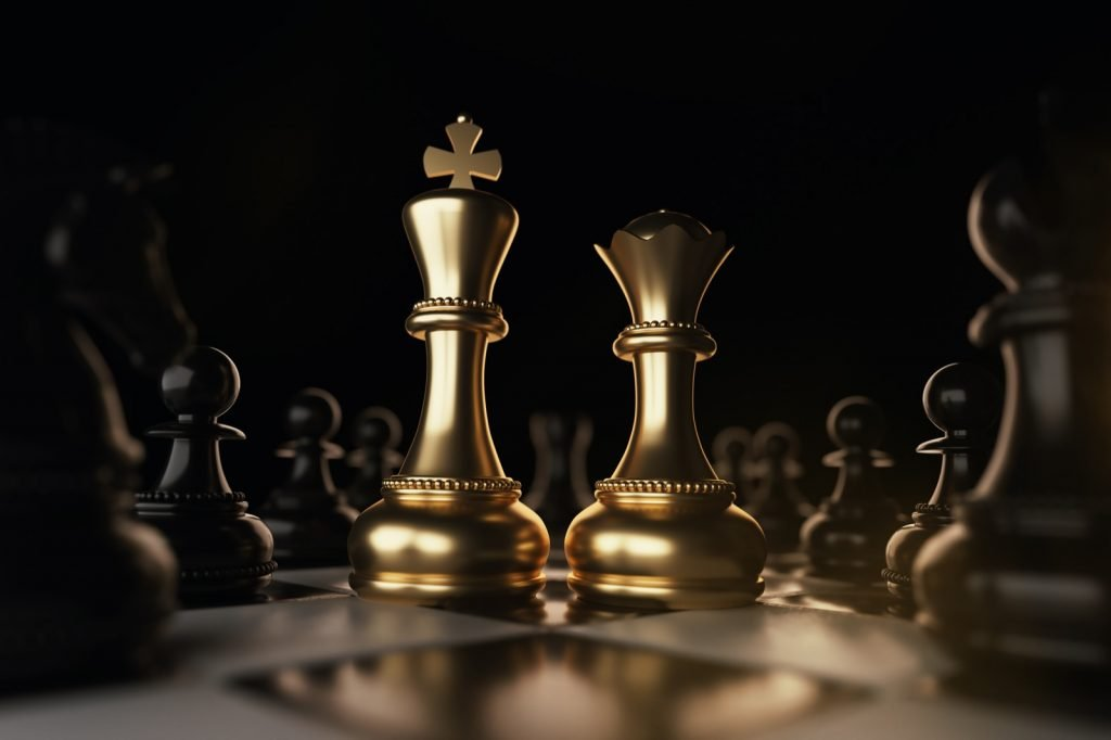Golden king and queen chess pieces symbolizing monarchy