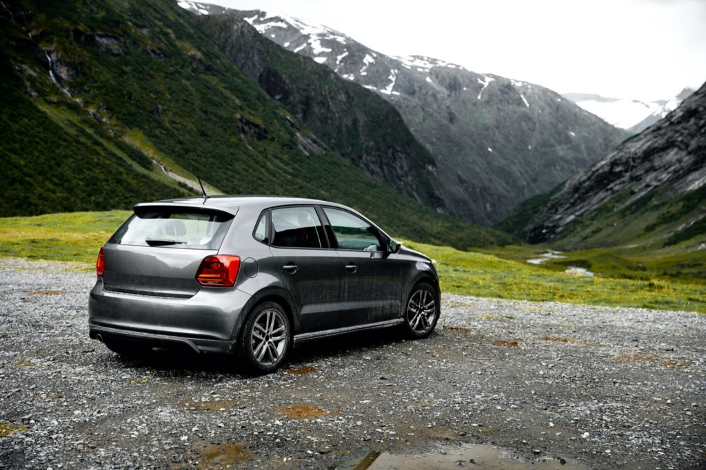 Gray car parking at a viewpoint in the mountains of Norway facing green valley