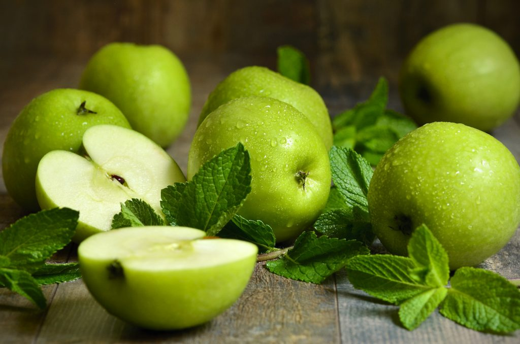 Granny Smith apples with dew on them lying on a wooden table with mint leaves as decor
