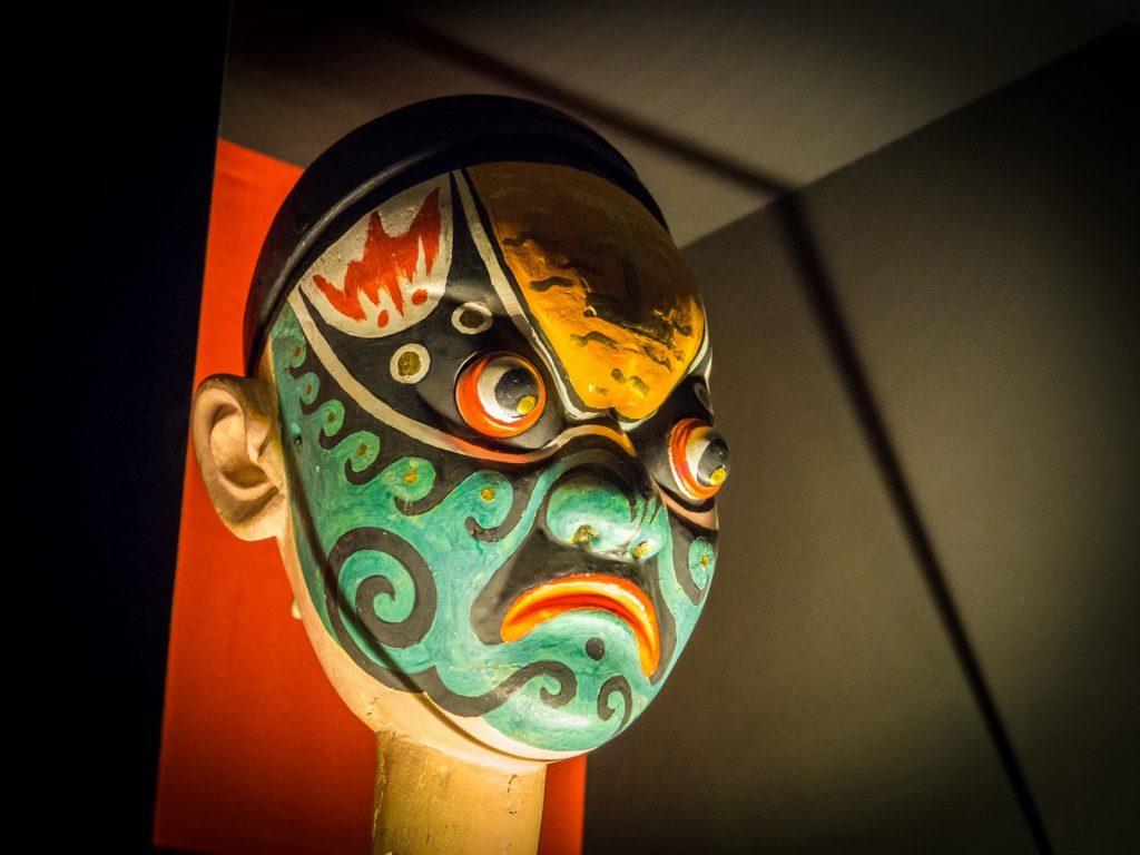 Traditional green Chinese opera mask sitting on a stick